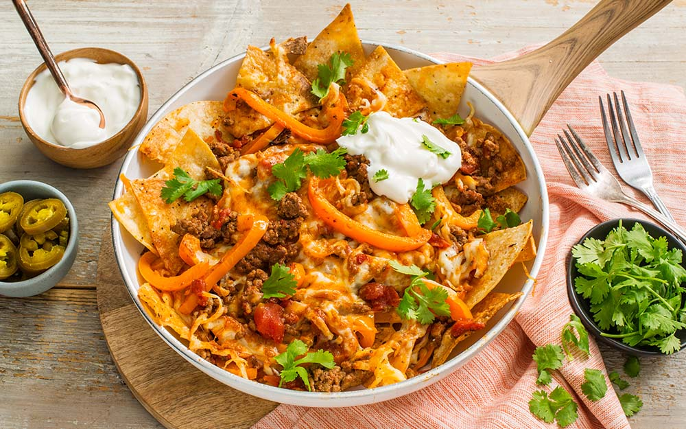 Beef & Cheese Chilaquiles with fire roasted tomatoes, corn tortillas and pickled peppers,