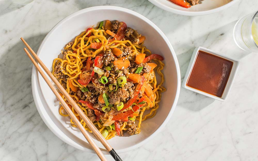 Asian Beef & Miki Noodles with a spicy sriracha-sesame sauce,