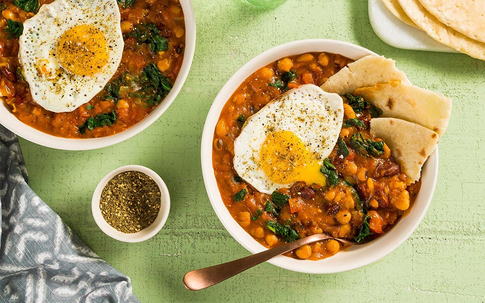 Middle Eastern Fasoulia Stew with beans, flatbread and a fried egg,
