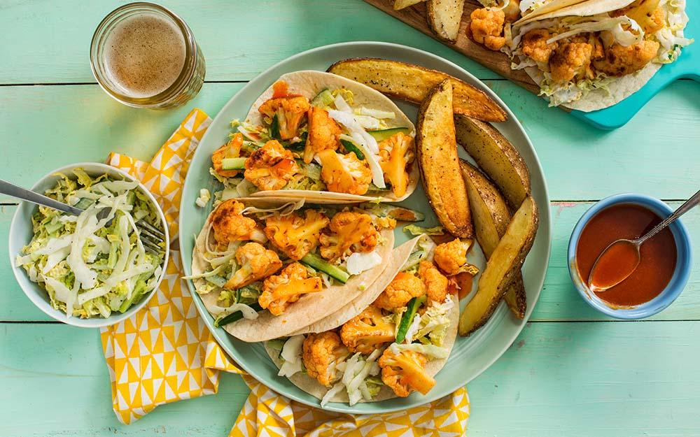 Honey Buffalo Cauliflower Tacos with roasted potato wedges and crunchy ranch salad,