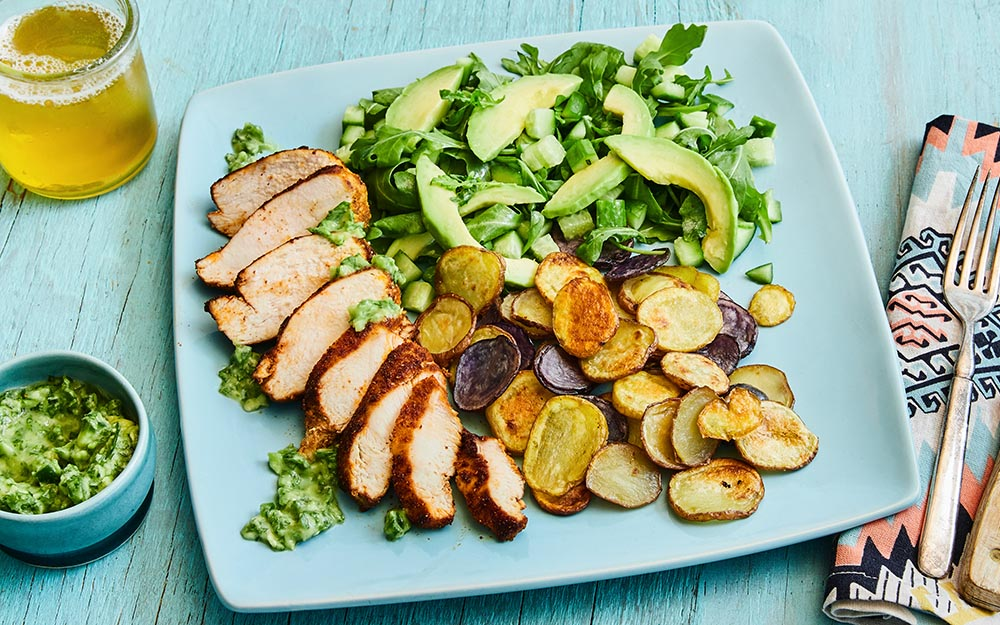 Peruvian Chicken with crispy potatoes, avocado green sauce and an arugula salad,