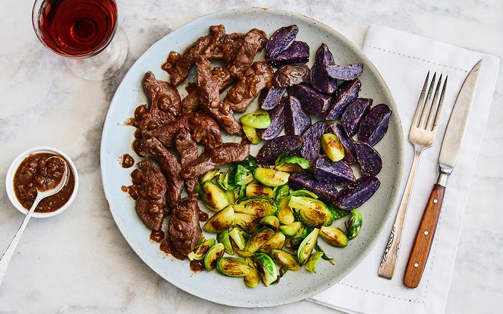 Striploin Steak & Red Wine Pan Sauce with garlic pepper purple potatoes and sautéed Brussels sprouts,